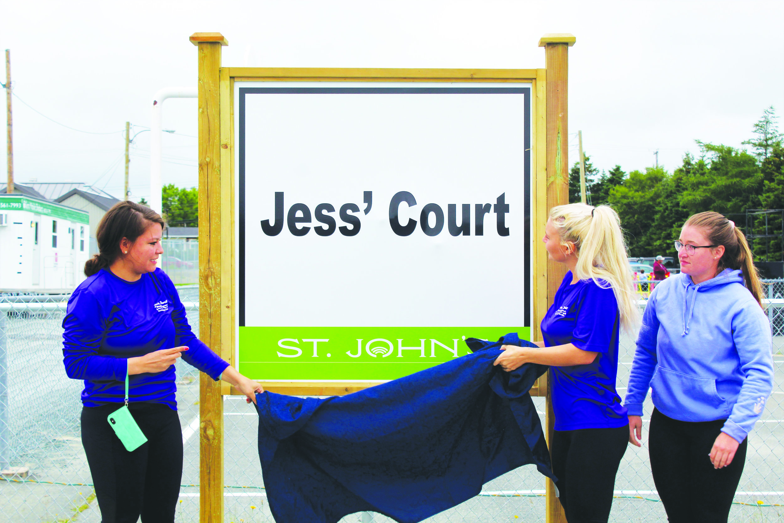 Shania Adams (left), Taylor Hayes (middle), and Rebecca Maher reveal the new sign during the official naming ceremony of Jess' Court. Chris Lewis photo