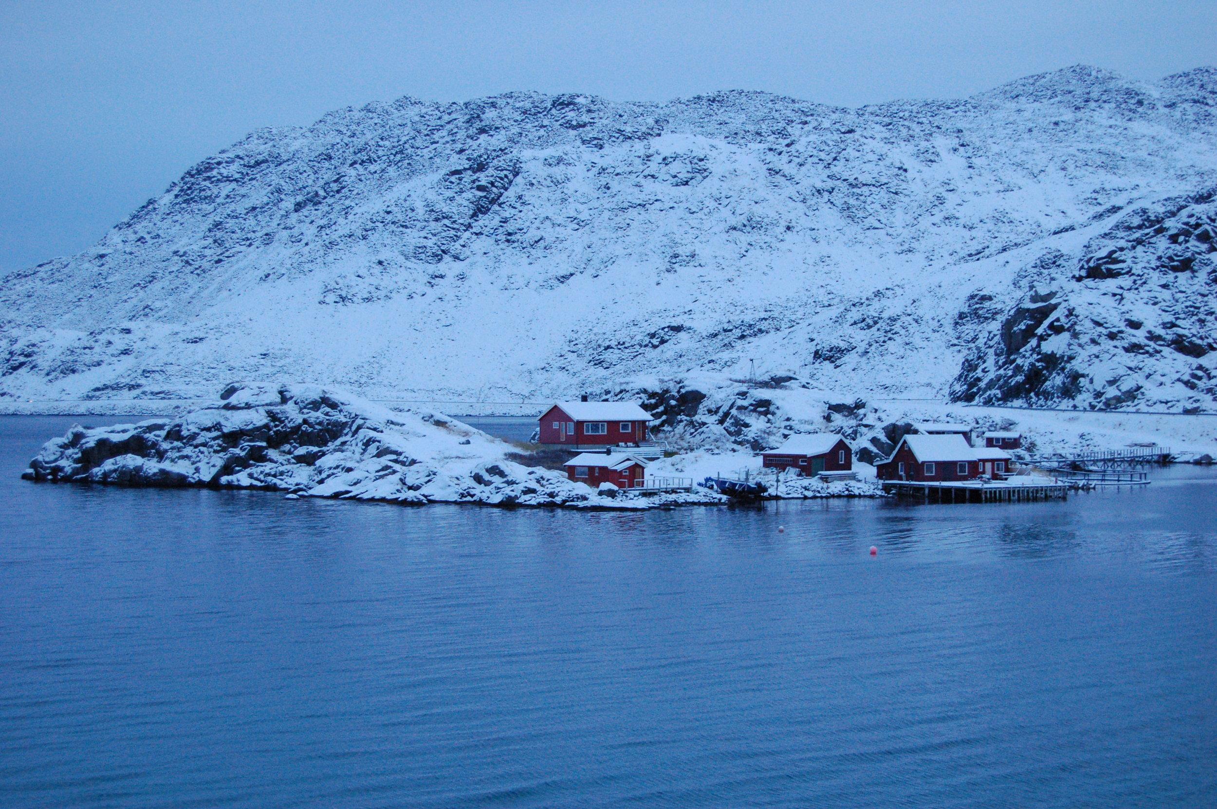 Eksempel på lokal klimatilpassing frå Nordkapp kommune. Bygningane er plassert i ly mellom to knausar ute på odden. Foto: Tore Kvande