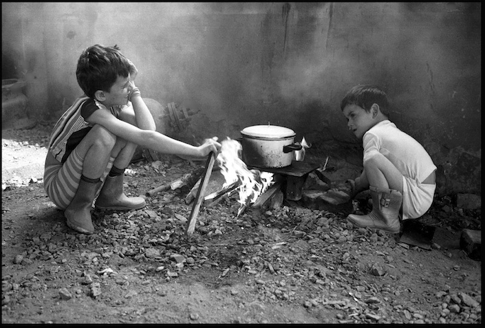 Kosovar refugees cooking in an abandoned warehouse near a refugee camp in Kukes, Albania.