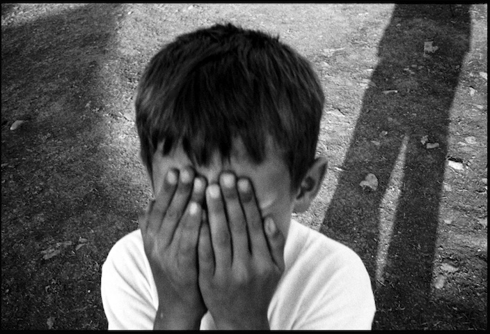 A boy playing hide and seek in Cegrane refugee camp, Macedonia.