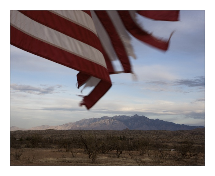A US flag tethered to a family gatepost flutters in the afternoon breeze on the road between Arivaca and Amado, in the background is the Santa Clara mountain range.