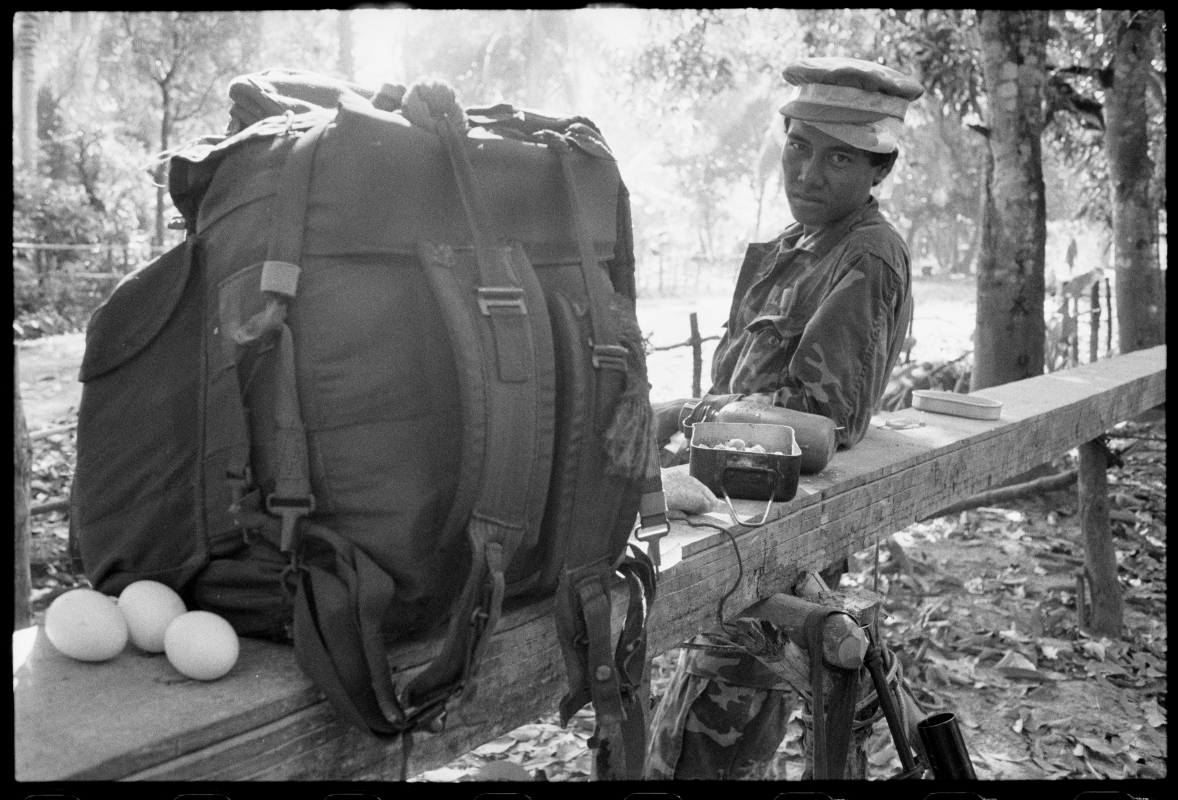 KPNLF soldier with 2 hats and 3 eggs. Cambodia, 1991