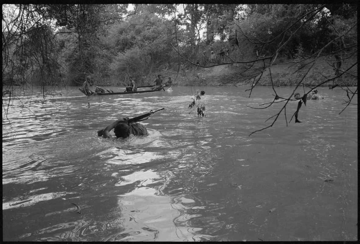 KPNLF soldiers cross a swollen river during a long range 6 week mission, Cambodia, 1991