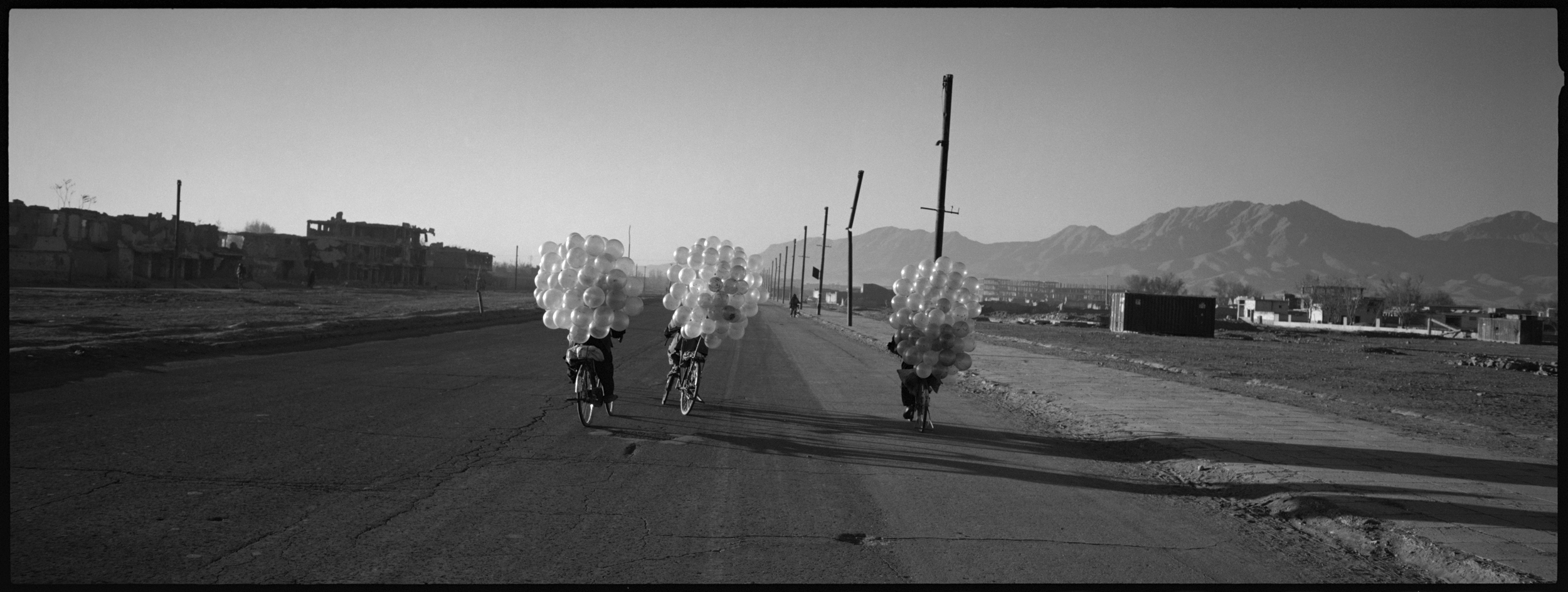 Cyclists selling balloons in one of the destroyed areas of Kabul. During the Taliban regime balloons were banned.
