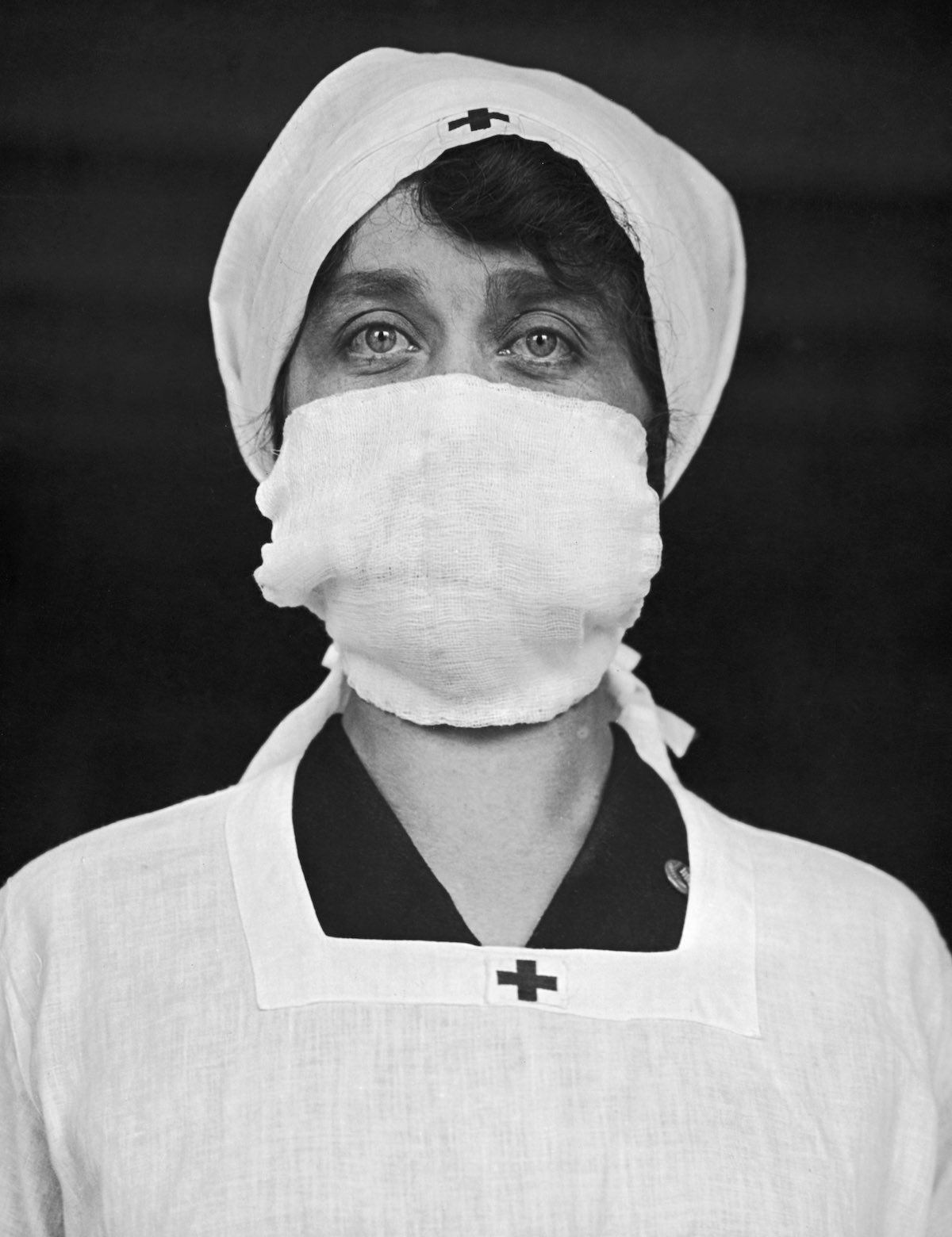 c. 1918 An American Red Cross employee wears a face mask in an attempt to help decrease the spread of influenza. IMAGE: PAUL THOMPSON/FPG/HULTON ARCHIVE/GETTY IMAGES courtesy of Mashable.