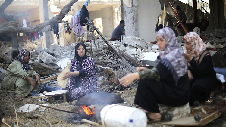 August 14: Palestinian women bake bread in front of the remains of their house in Khan Younis, in the southern Gaza Strip. ©Reuters/I. Abu Mustafa