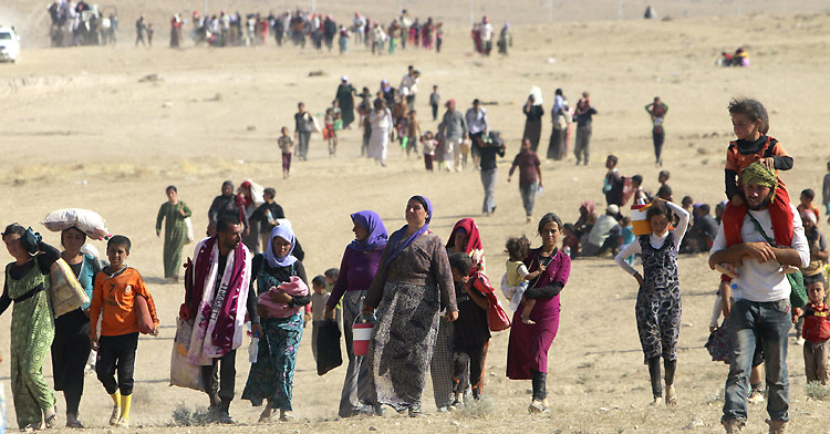 People fleeing violence in the town of Sinjar head for the Syrian border. ©Reuters / R. Sai