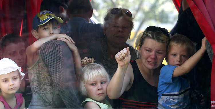Residents of the eastern Ukrainian region of Donetsk look out of a bus window as they prepare to depart to escape the fighting. ©Reuters/M. Zmeyev