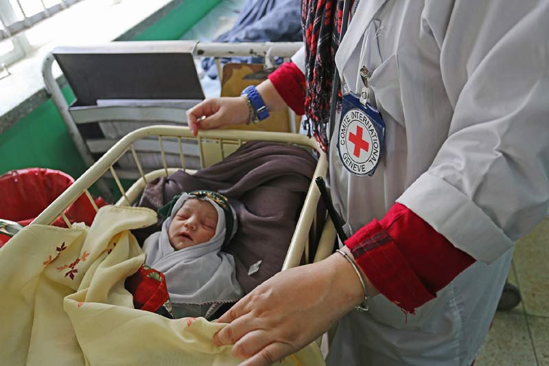 An ICRC senior medical officer checks on a baby who was delivered by C-section. Where there is no safe access to health care locally, women who have had complications often endure long and painful journeys over dangerous roads to reach help. ICRC/W Carter