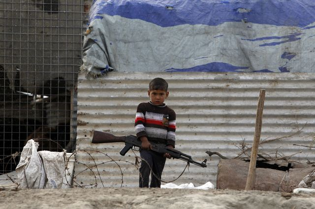 ATT - What remains to be done - Boy With AK-47, Iraq - Photo courtesy of Reuters/Thaier Al-Sudani