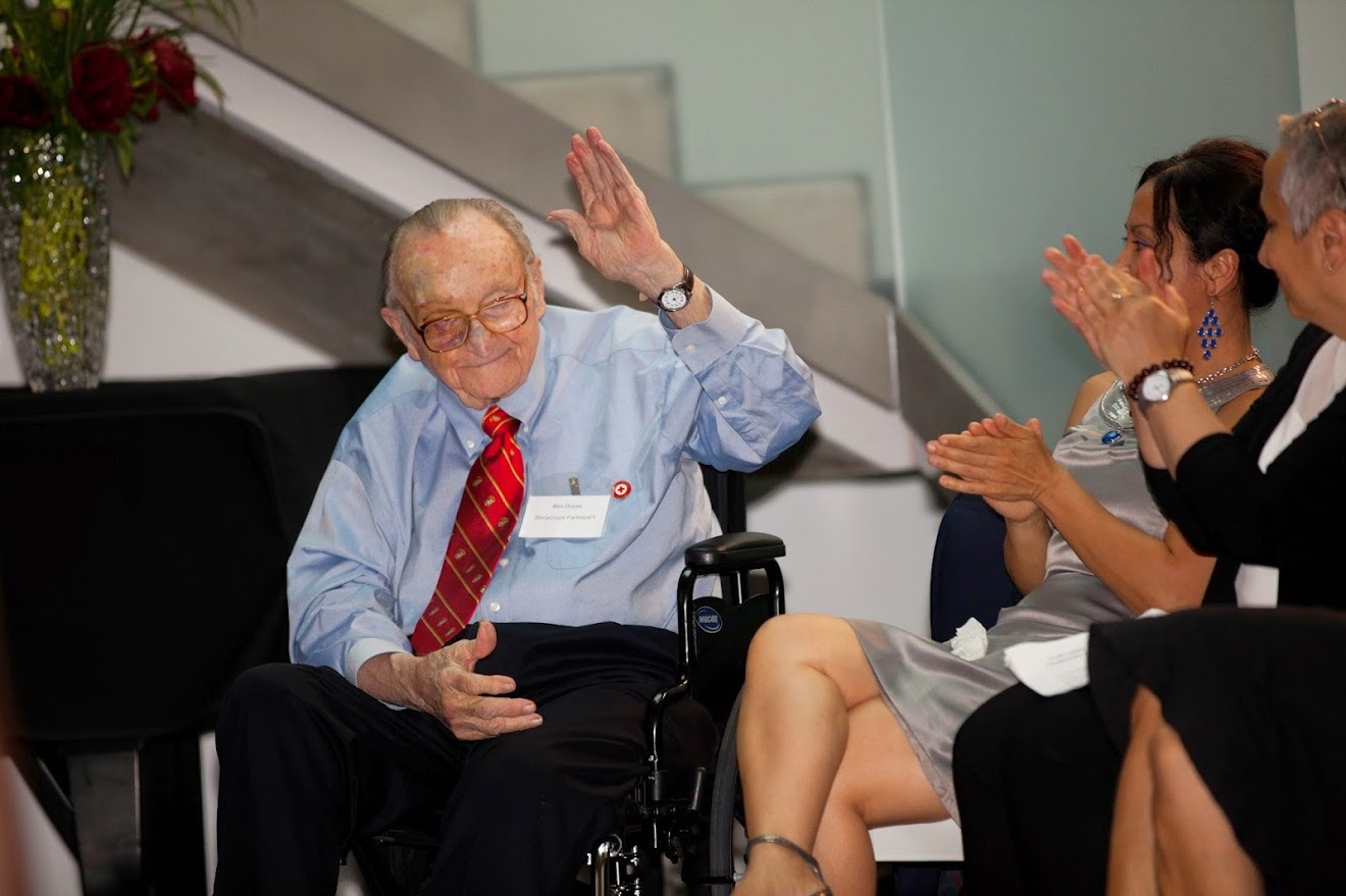 StoryCorps Participant and World War II Veteran, Ben Dozier, receives a round of applause from the audience after they heard his story about finding his daughter MeiLee (seated next to him) at a Red Cross refugee camp in Guam following the end of the Vietnam War.