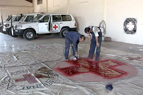 ICRC employees in Amman painting a large emblem on a tarpaulin intended to cover trucks bringing aid from Jordan to Iraq.