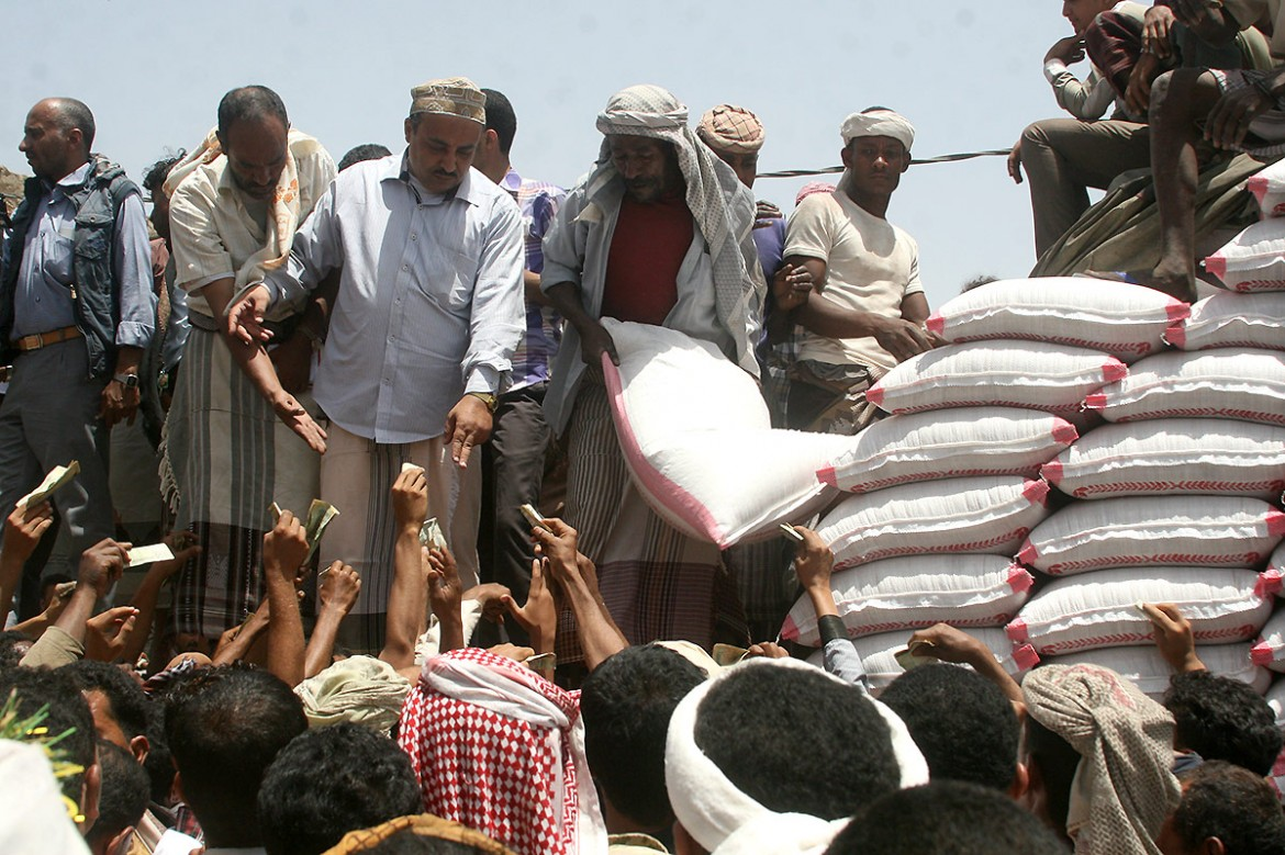 Taiz, Demna area.  Dozens of people line up in blistering heat to buy wheat amid extreme food shortages across the country. Ninety percent of the country's food is imported; but restrictions mean most of it cannot be brought into the country.  CC BY-NC-ND/ICRC/A. Mahyoub