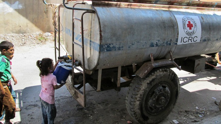 Homs, Syria. A displaced girl stocks up on water from an ICRC water truck. CC NY-NC-ND/ICRC/SY-E-00308