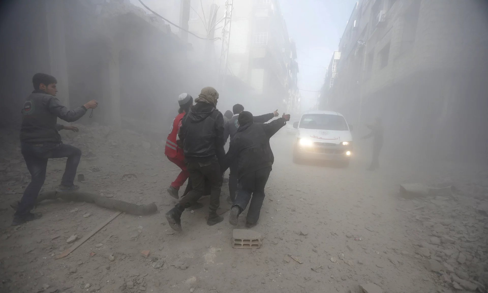 Residents and a member of the Syrian Red Crescent carry an injured man, after an air-strike in eastern Ghouta. The ICRC explains to warring parties practical ways to reduce civilian deaths. ©Bassam Khabieh/Reuters