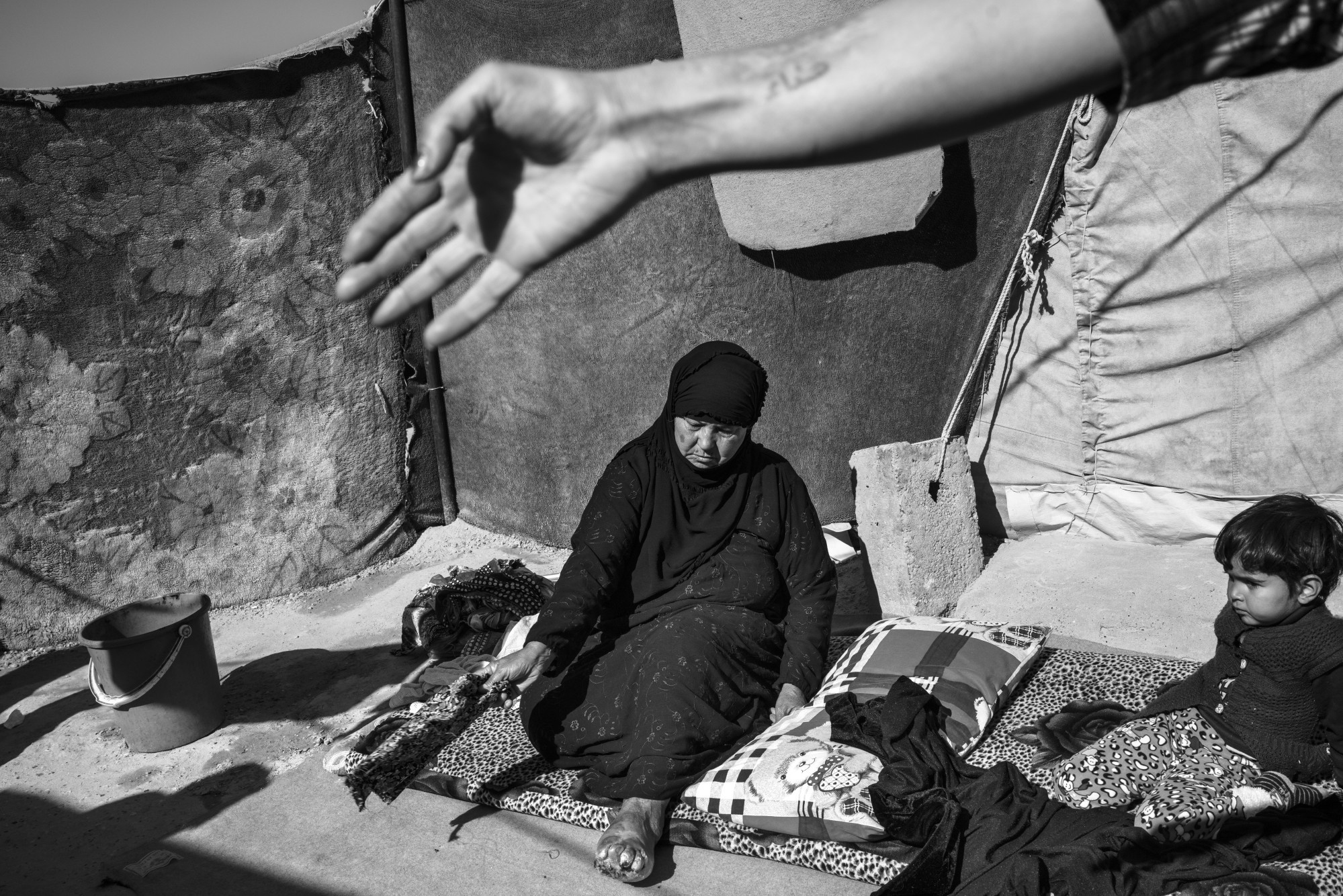 Abda Dayeh Hamadi, 60, sits outside her tent at camp Markazi, in Anbar Province, where many internally displaced families have come from Fallujah and Ramadi. A diabetic, Abda suffers from gangrene in her left foot and has no access to health care anymore. Moises Saman/Magnum Photos for ICRC