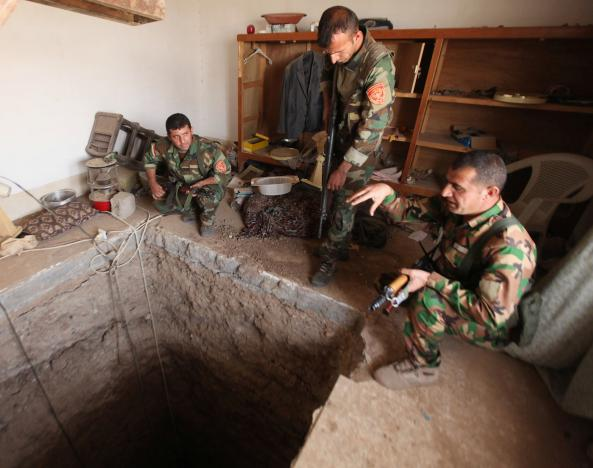 Peshmerga forces stand around a tunnel believed to beused by the Islamic State Group on the outskirts of Bartila. REUTERS/Azad Lashkari