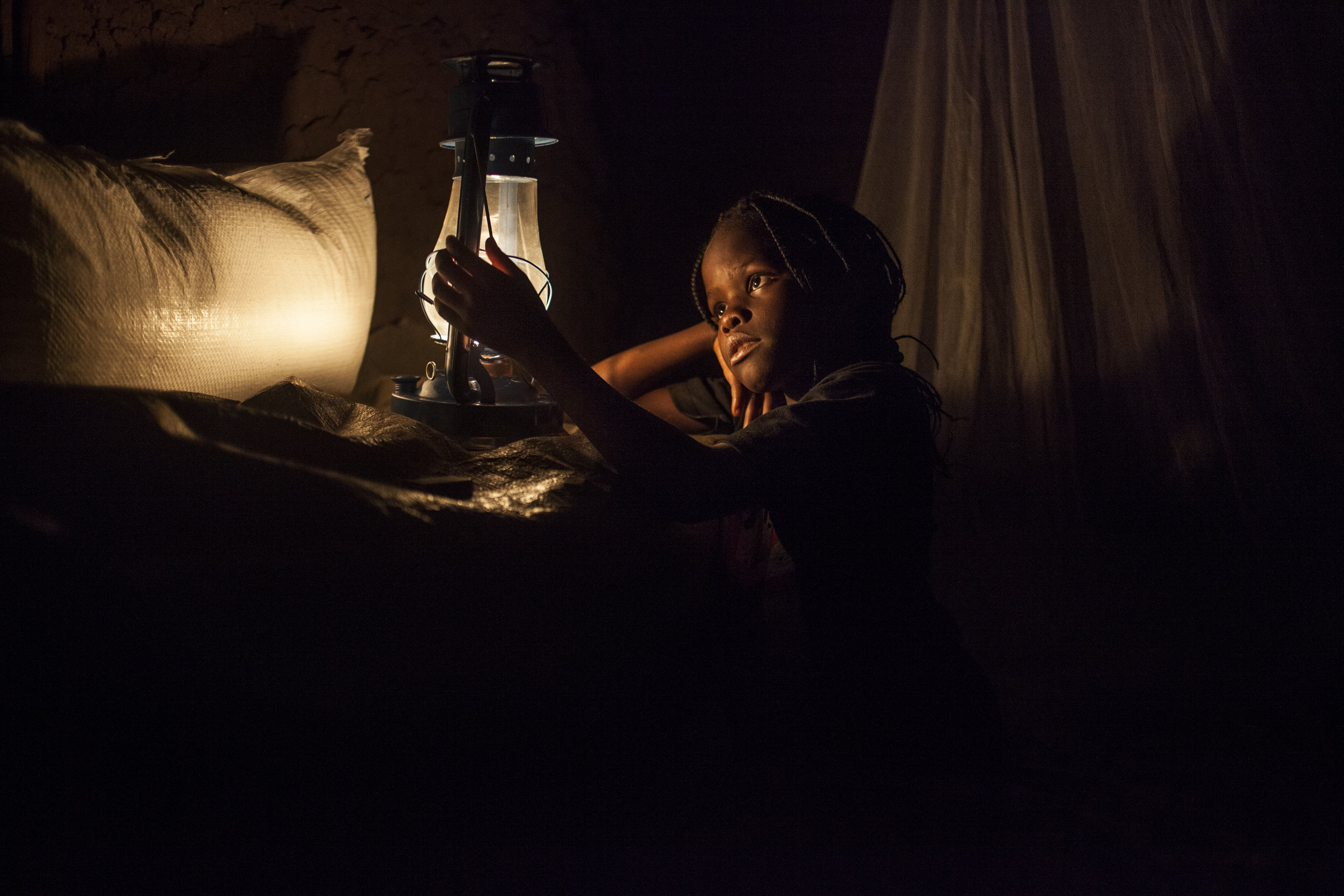 A girl admires the kerosene lamp alight in her grandmother's mud home, with whom she and her sister were reunited by ICRC's global family tracing team following the death of their parents during the Rwandan genocide in 1994.
