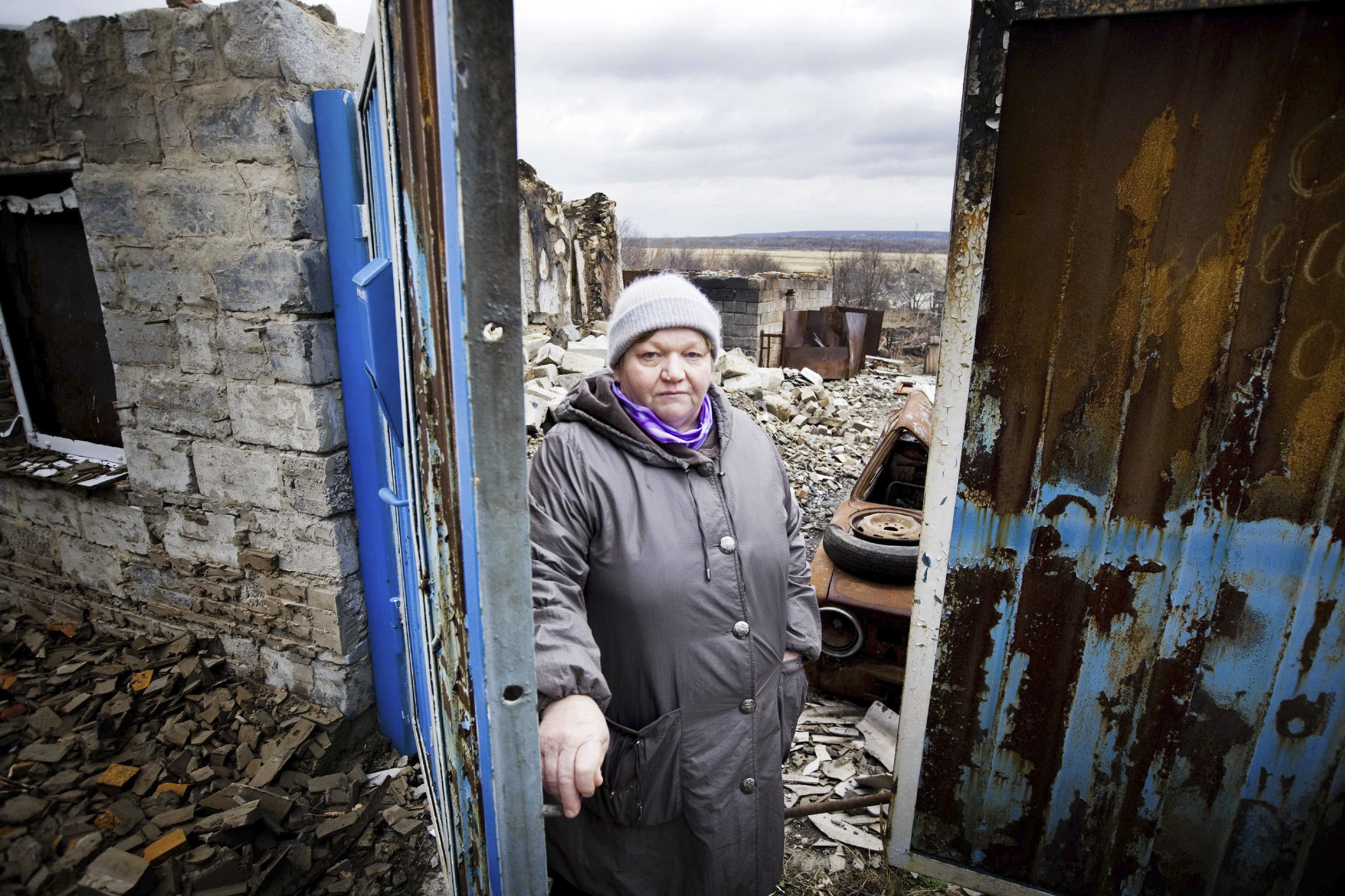 Lugansk, Bolshaia Vergunka village, Ukraine. The ICRC distributes construction materials to residents, including Valentina, pictured, to reconstruct their houses. Here, Valentina stands in front of the ruins of her house, where her husband was killed, due to the proximity to the front line.