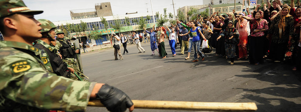 Ethnic Uyghur women protest towards Chinese riot police in Urumqi in China's far west Xinjiang province on July 7, 2009. (PETER PARKS/AFP/Getty Images)