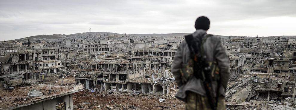 A Kurdish marksman stands atop a building looking at the destroyed Syrian town of Kobane, also known as Ain al-Arab, on January 30, 2015. (BULENT KILIC/AFP/Getty Images)