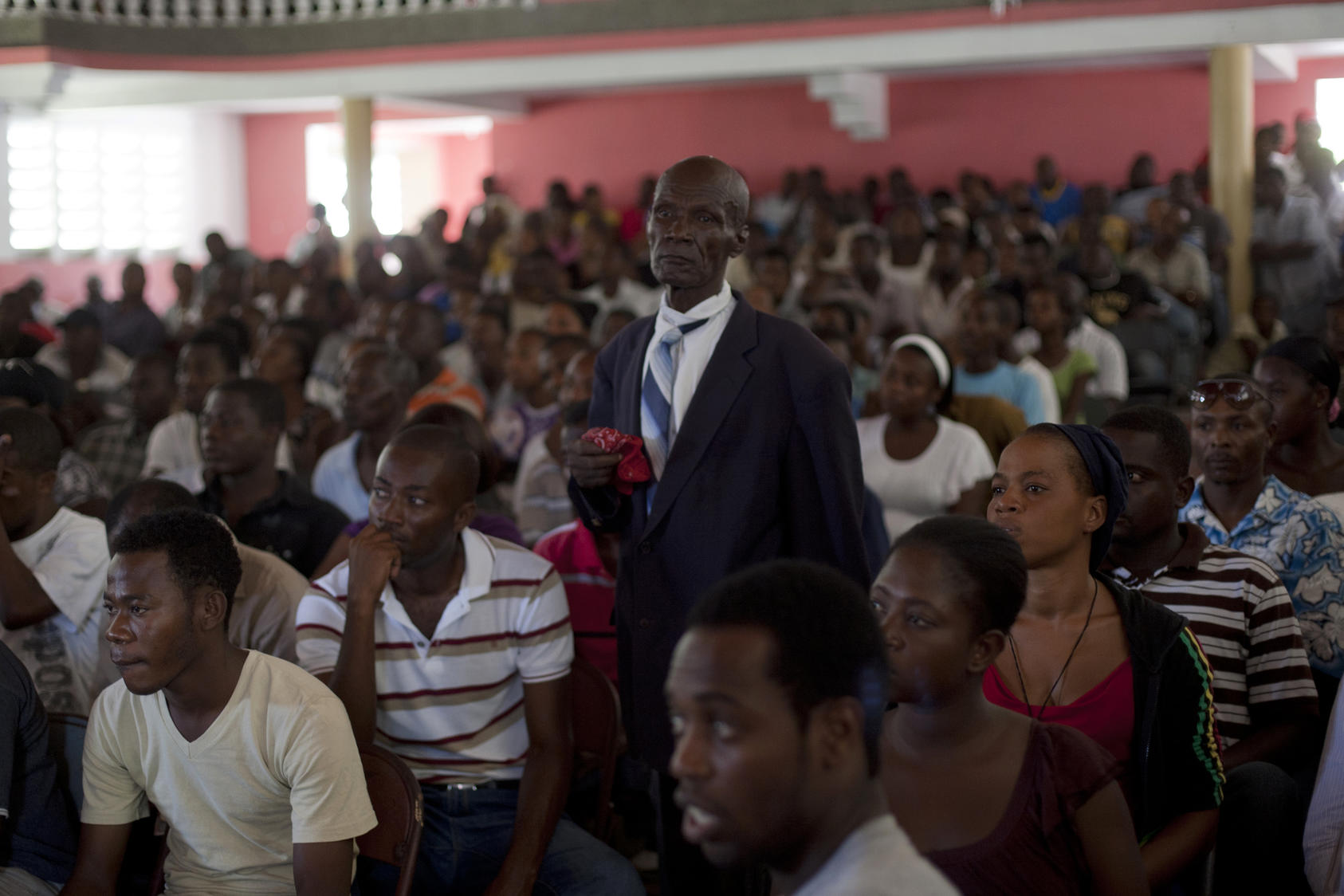 Audience of a courtroom during a trial of police officers, who are charged with murder or attempted murder for a prison massacre, at the Catholic Cultural Center Saint-Louis in Haiti, Oct. 2011. Photo Courtesy of The New York Times/Andres Martinez Casares