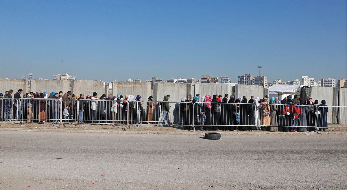 Syrian refugees line up to register with the UNHCR in Tripoli, Lebanon.