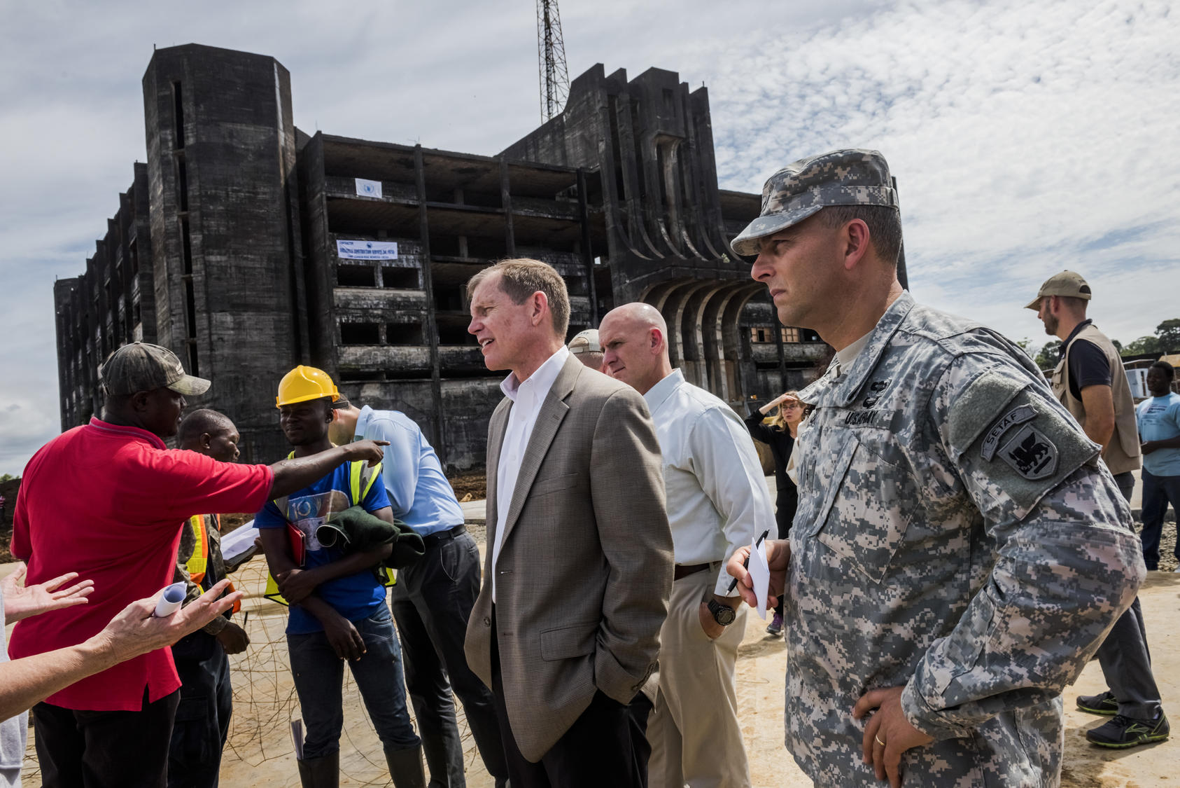 The former U.S. assistant secretary of defense for special operations and low-intensity conflict, and a U.S. delegation tour a construction site of an Ebola treatment center in Liberia, Oct. 2014. Photo Courtesy of The New York Times/Daniel Berehulak