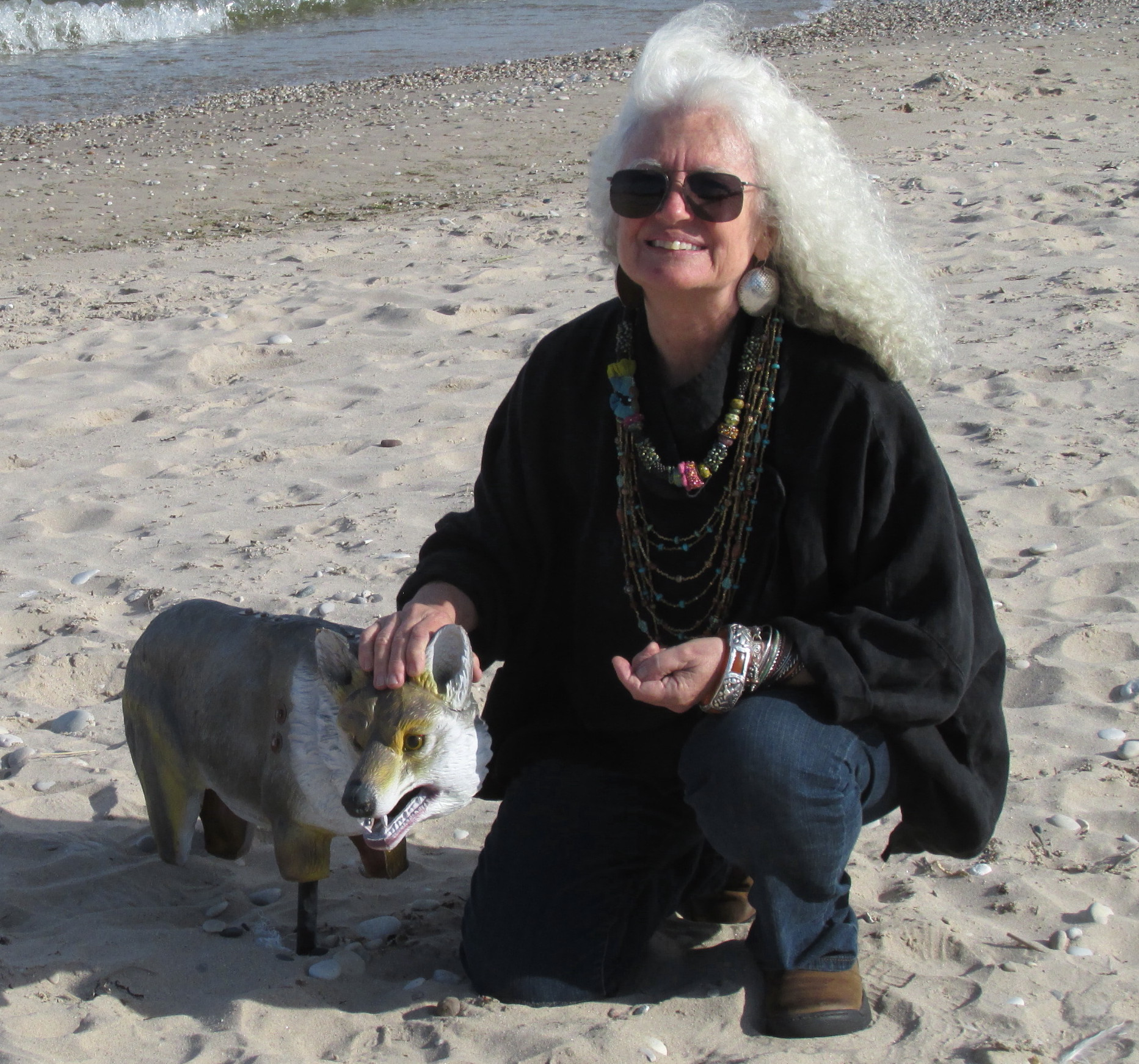 Judie on the beach visiting with one of the rubber foxes that inhabit the sand to help keep away the birds.