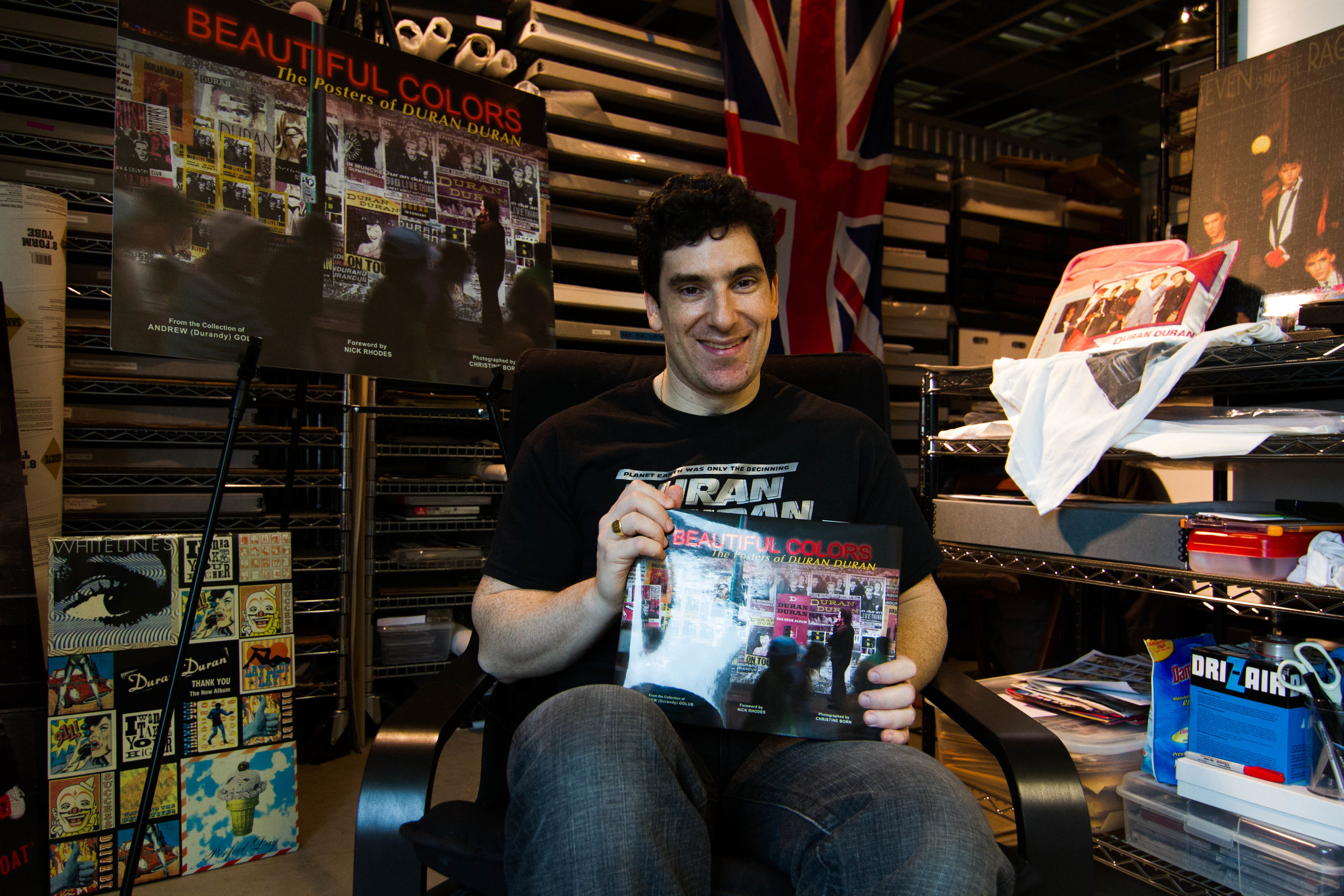 """Andrew """"Durandy"""" Golub, 42, poses with his newly written book """"Beautiful Colors"""" on Saturday afternoon, April 5, 2014. The book is comprised of a collection of Duran Duran's posters throughout their career. Golub has become a well-known archivist of Duran Duran memorabilia. He houses his in a storage unit in Bellevue, Wash."""