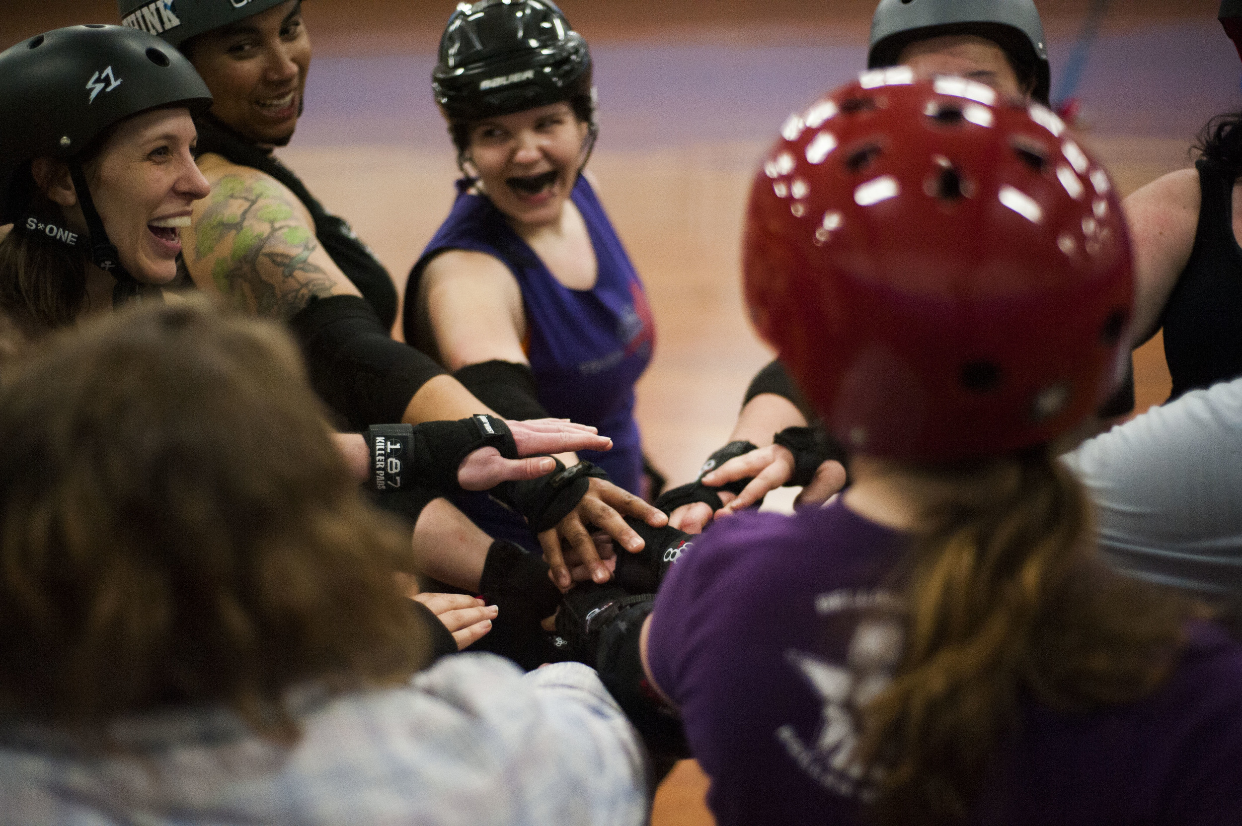"""Hot, tired and sore the Bellingham Roller Betties team Tough Love brings their hands in for a cheer at the end of their late night practice. The women of the Roller Betties train hard and work together to become a tight-knit cohesive team. Hadassah """"H'Elanna Torrez"""" McGill (center) leads the post-practice chant, surrounded by her teammates."""