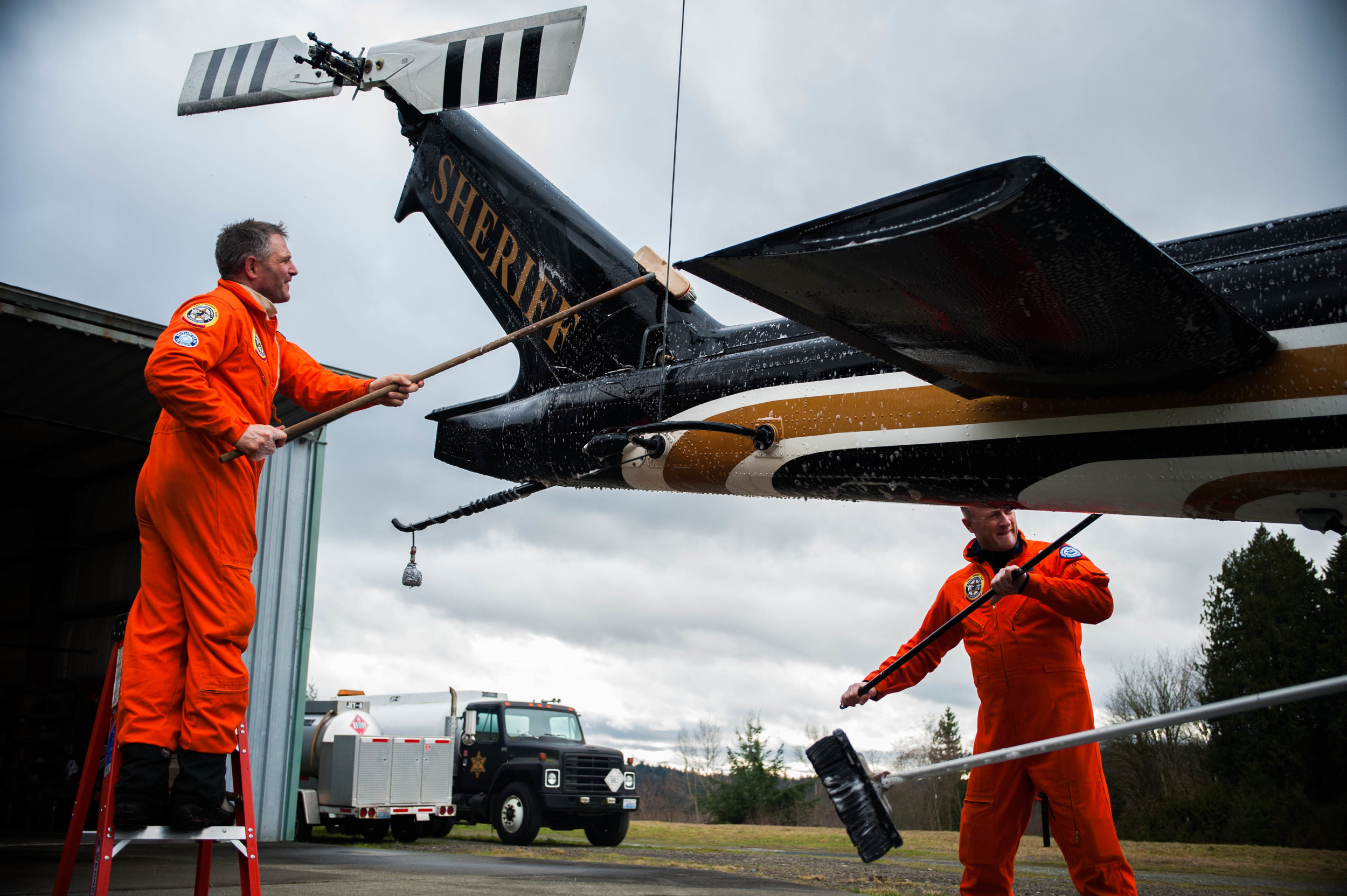 Ernie Zeller (left) and Oyvind Henningsen (right) help to clean SnoHawk 10 following a rescue training exercise in the mountains. Upon landing and securing the main rotor blades the entire five-man crew sets to work on their post-flight duties of cleaning and checking all aspects of the UH-1H helicopter.
