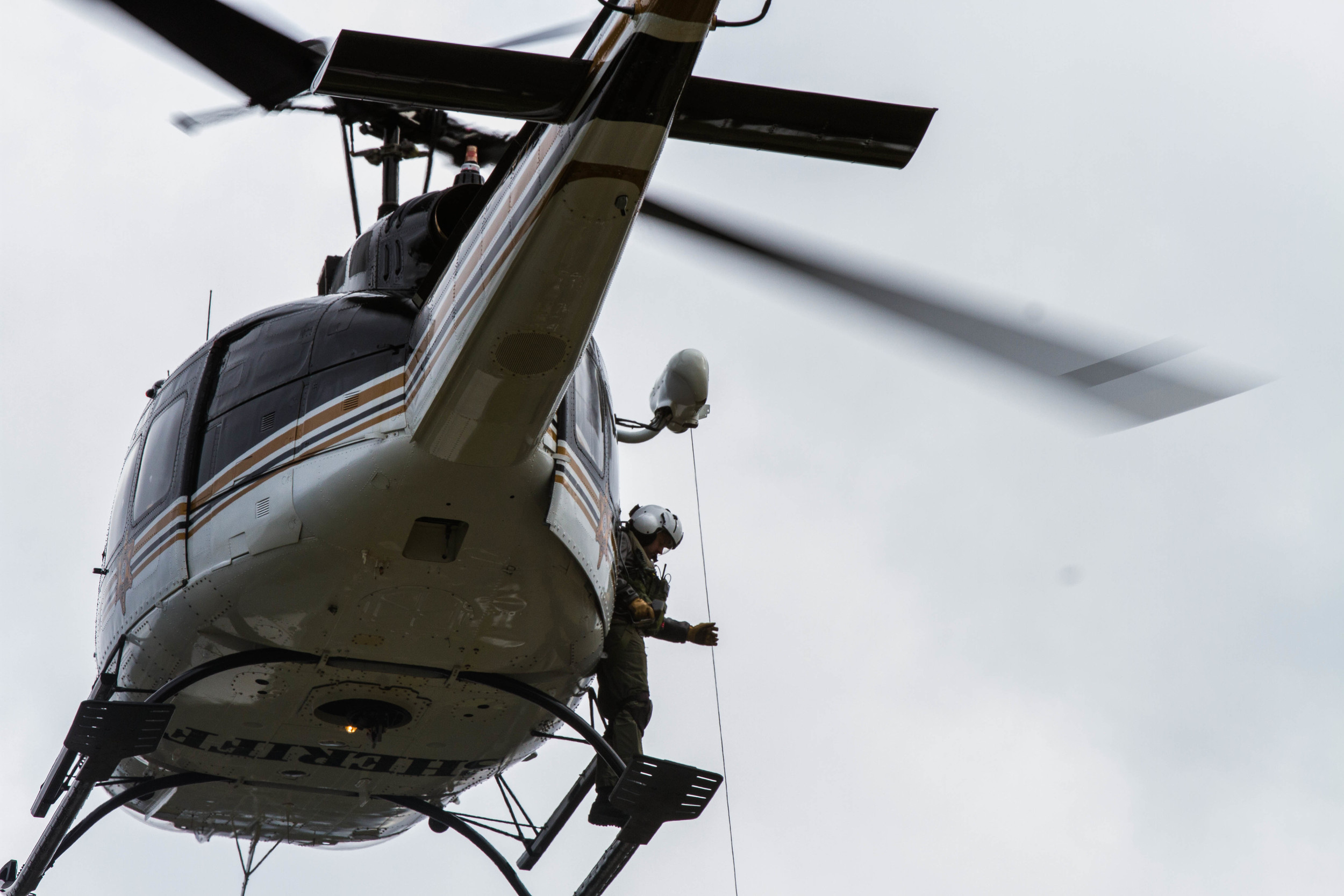 Crew chief, Deputy Beau Beckner, stands outside of SnoHawk 10 to operate the hoist during a training session with the Snohomish County Search and Rescue Helicopter Rescue Team.
