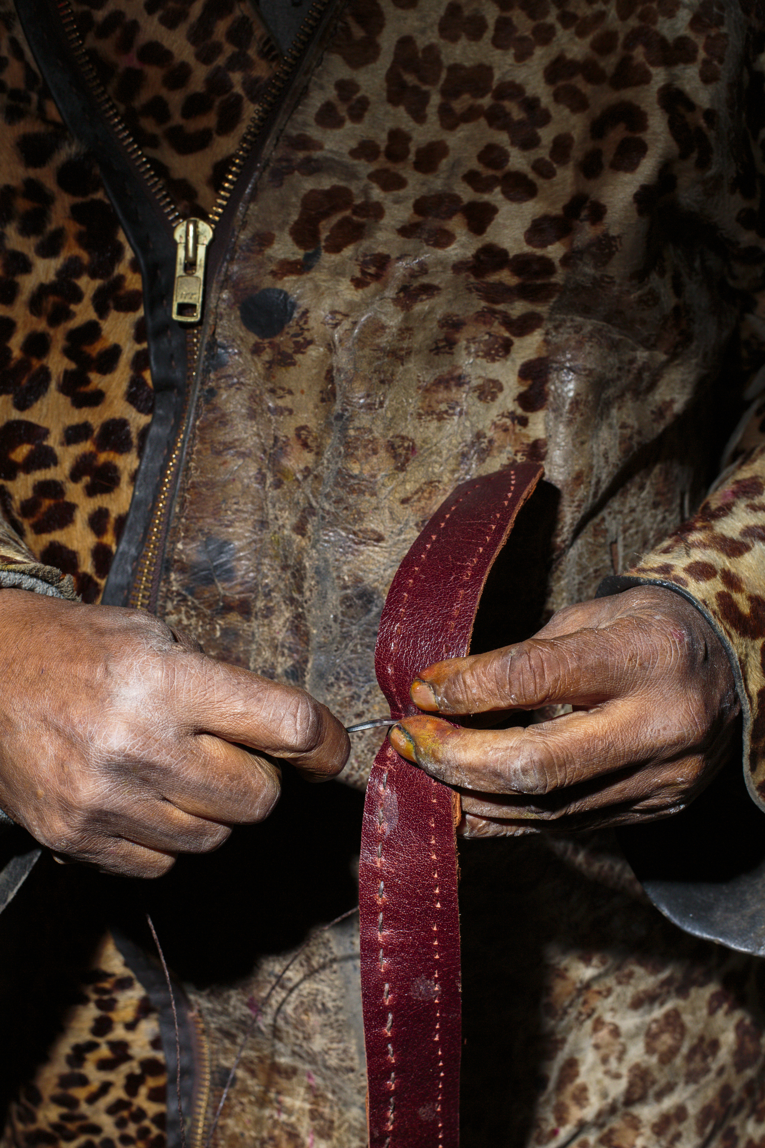 New York, USA - October 31, 2015: The hands of street vendor James are seen while he crafts a leather belt. He sells his goods every night on a small table on 25 1st Ave. The Bowery, a street and neighborhood in Manhattan, once home for vagrants and a diversity of subcultures became the playground of artists, fancy bars and real-estate tycoons.