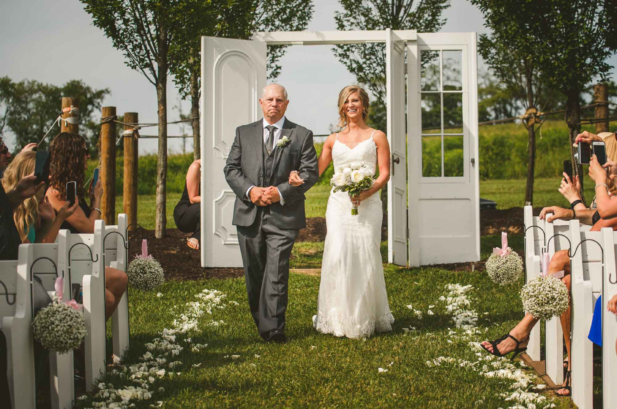 Bride and father walking down aisle at wedding ceremony