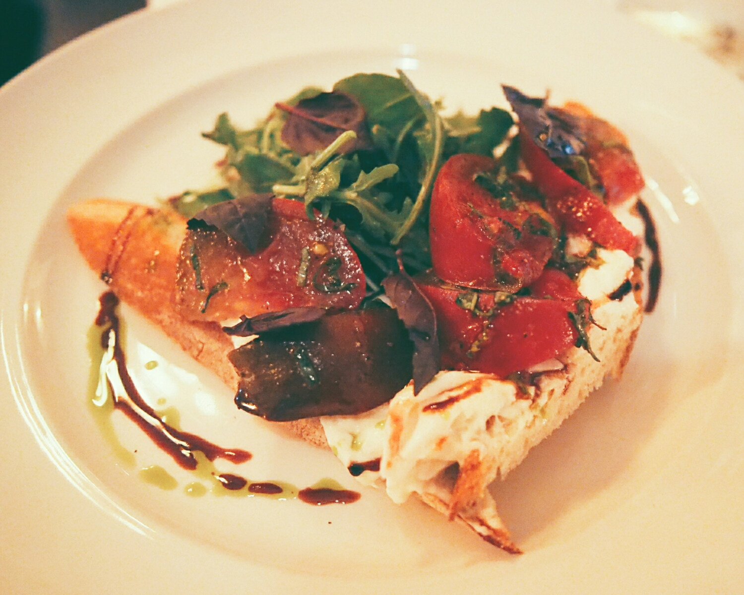 burrata caprese  with heirloom tomato, basil, mint, aged balsamic, arugula, extra virgin olive oil on baguette.