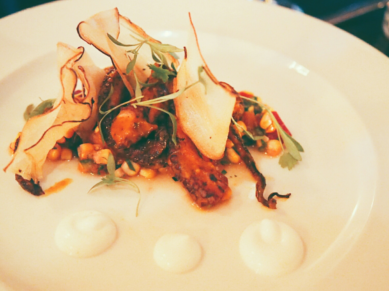 crispy barbecued octopus  with peach and corn salad, serrano chile, cilantro, lemon creme fraice, yucca crisps.