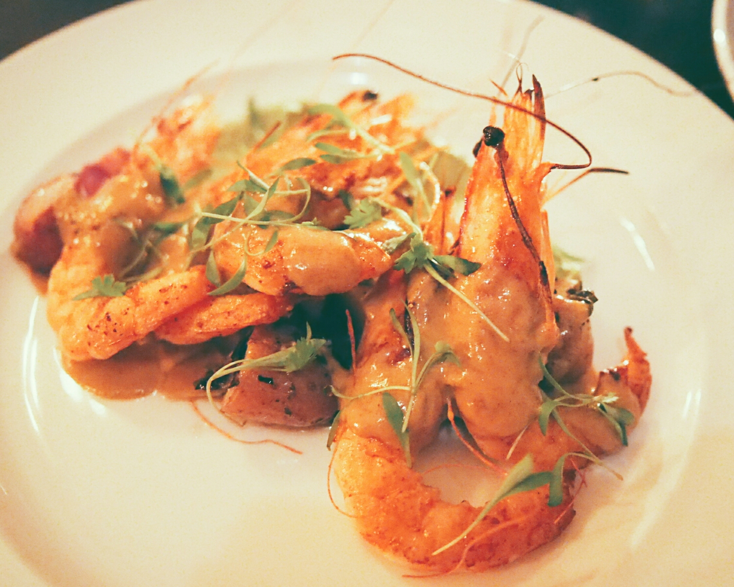 caledonia salt prawns  with charred spring onion, fingerling potato, avocado puree, crispy bacon, bisque cream.