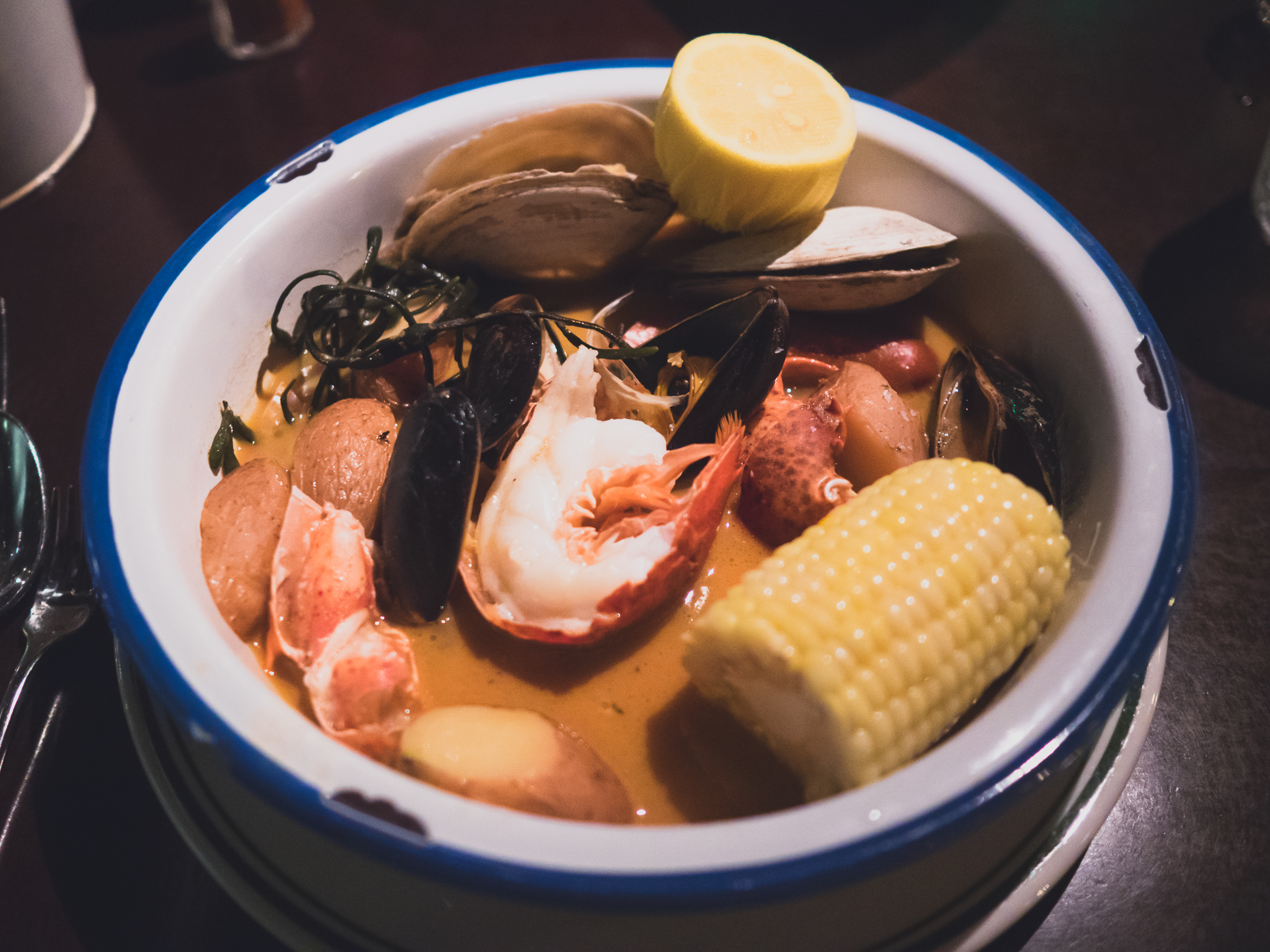 new england boiled dinner  with mussels, steamers, lobster, linguiça, potatoes, steamed corn.