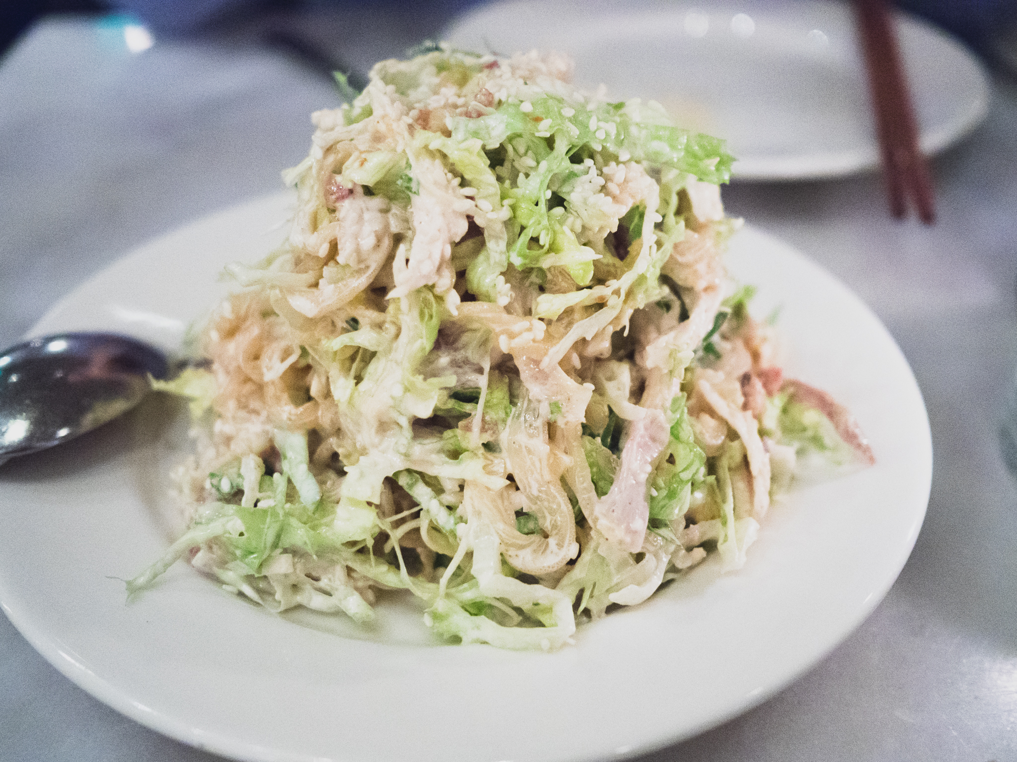 jellyfish salad  with shredded chicken, crispy rice, green leaf, sesame bacon dressing.