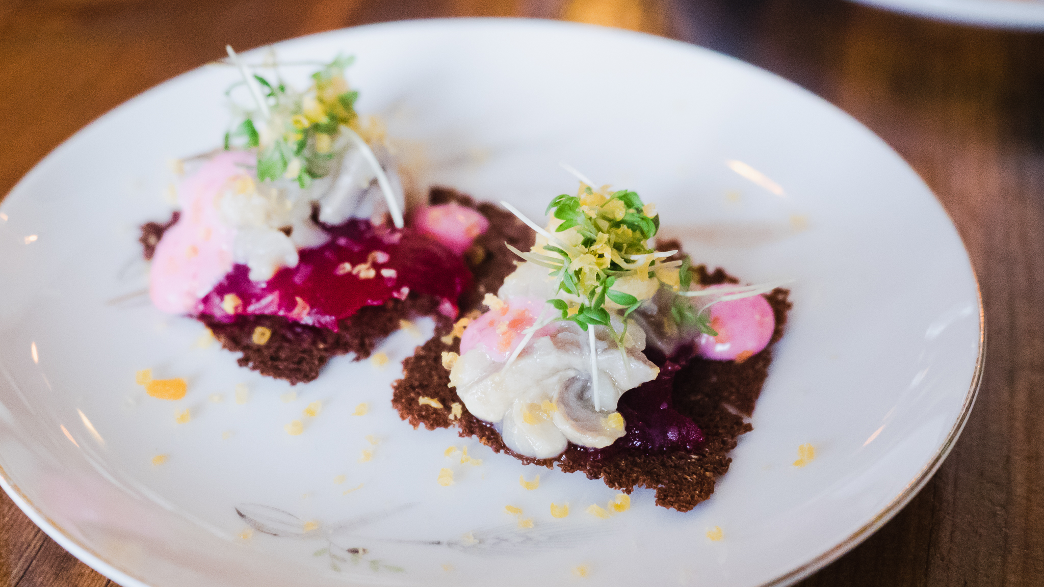 course 3, seafood menu. pickled herring, rye bread, beets and cured egg yolk.