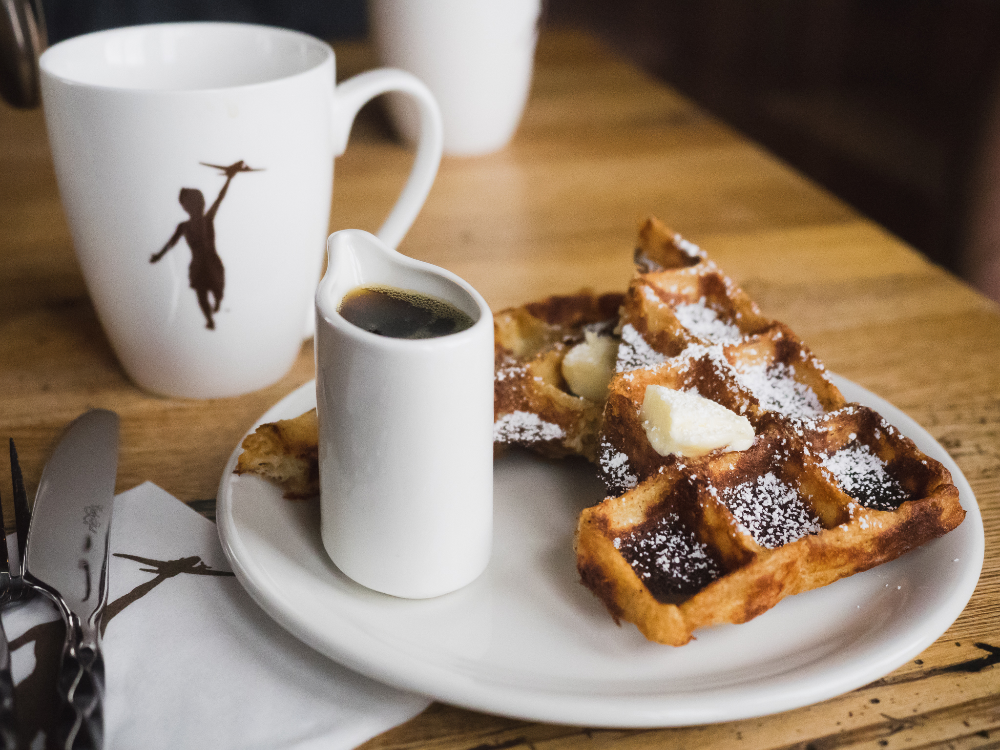 french press coffee and a waffle with butter, powdered sugar and maple syrup.