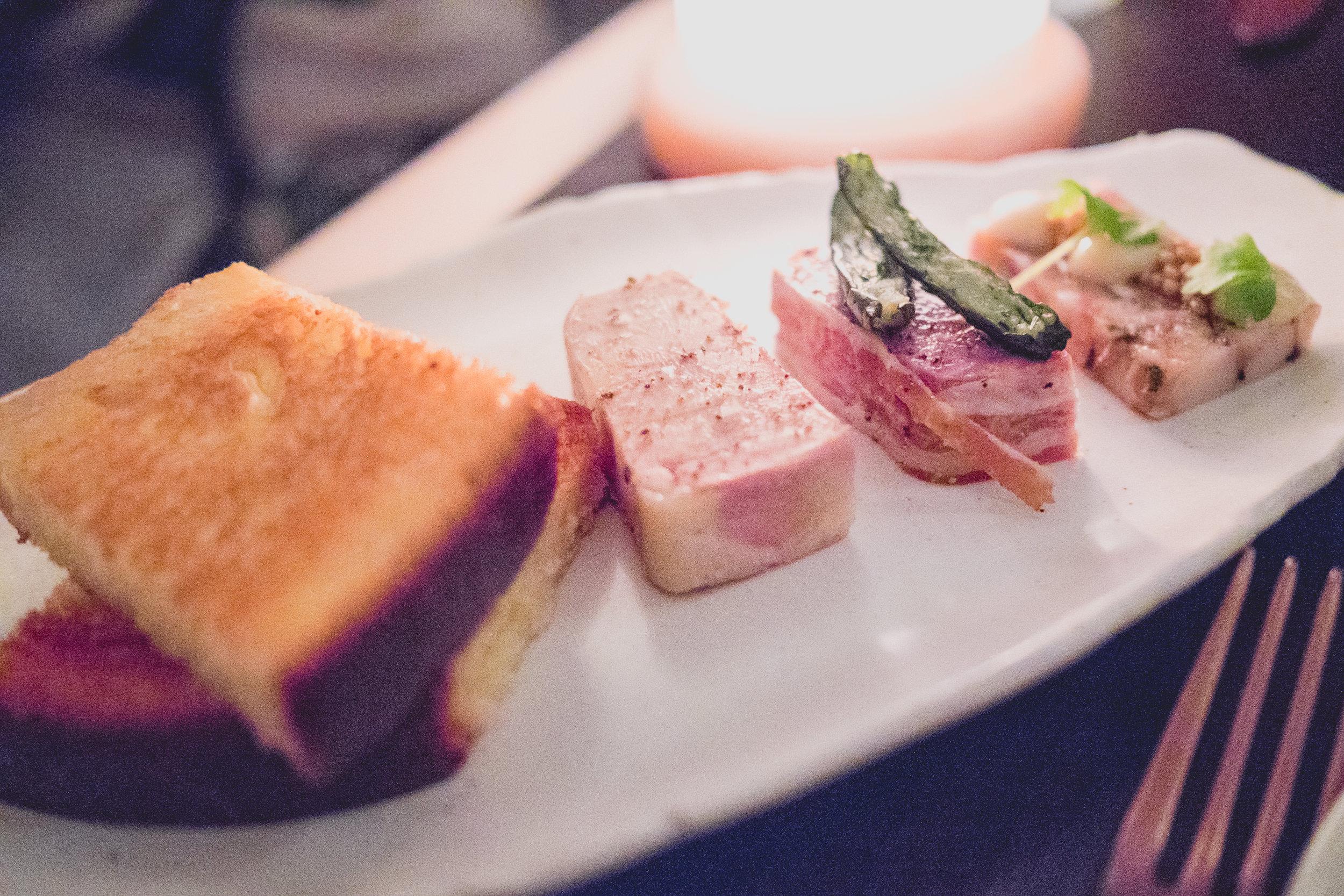 toasted brioche;   foie gras terrine;   pork and liver terrine  wrapped in proscuitto;  tete de cochon .
