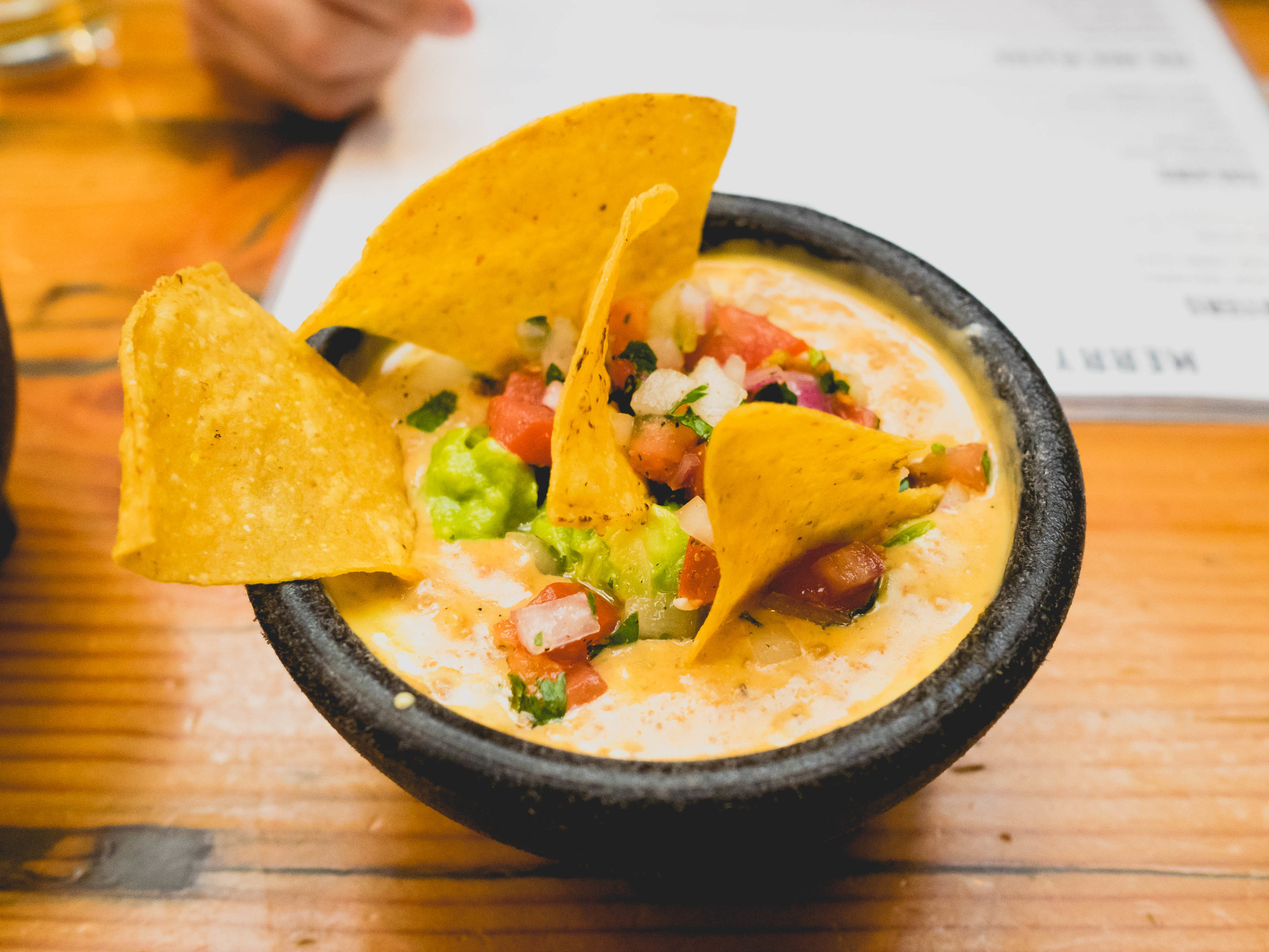 twisted cowgirl dip : queso mixed with ground beef and topped with guacamole & pico de gallo.