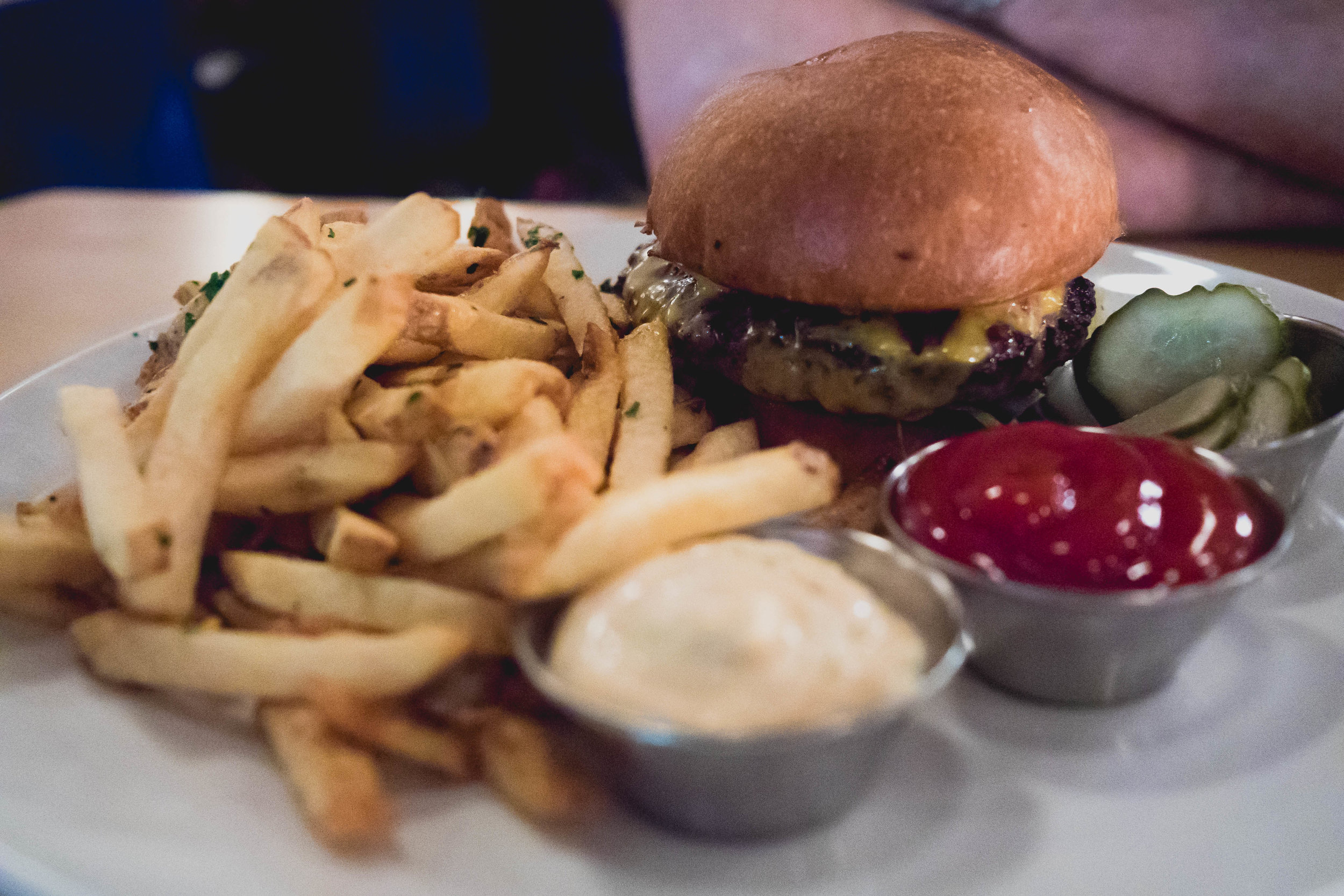 cheeseburger  with house sauce, cheddar, pickles, iceberg, grilled onion, brioche, fries.