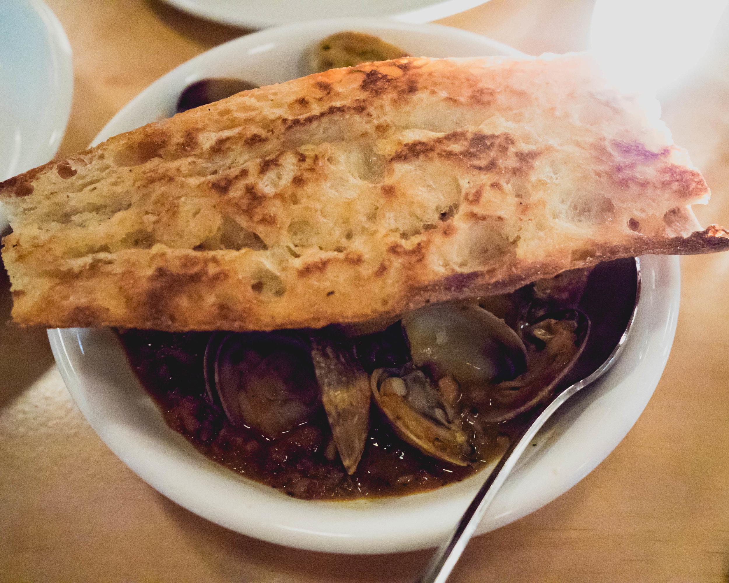 clams , merguez sausage, white beans, cavolo nero, sofrito, baguette.