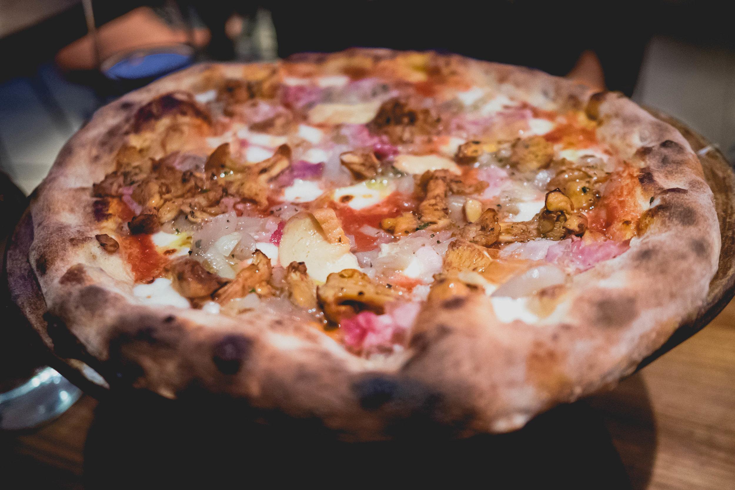 chanterelle mushrooms  pizza with tomatoes, house made mozzarella, prosciutto cotto, smoked buffalo, provola, shallots.