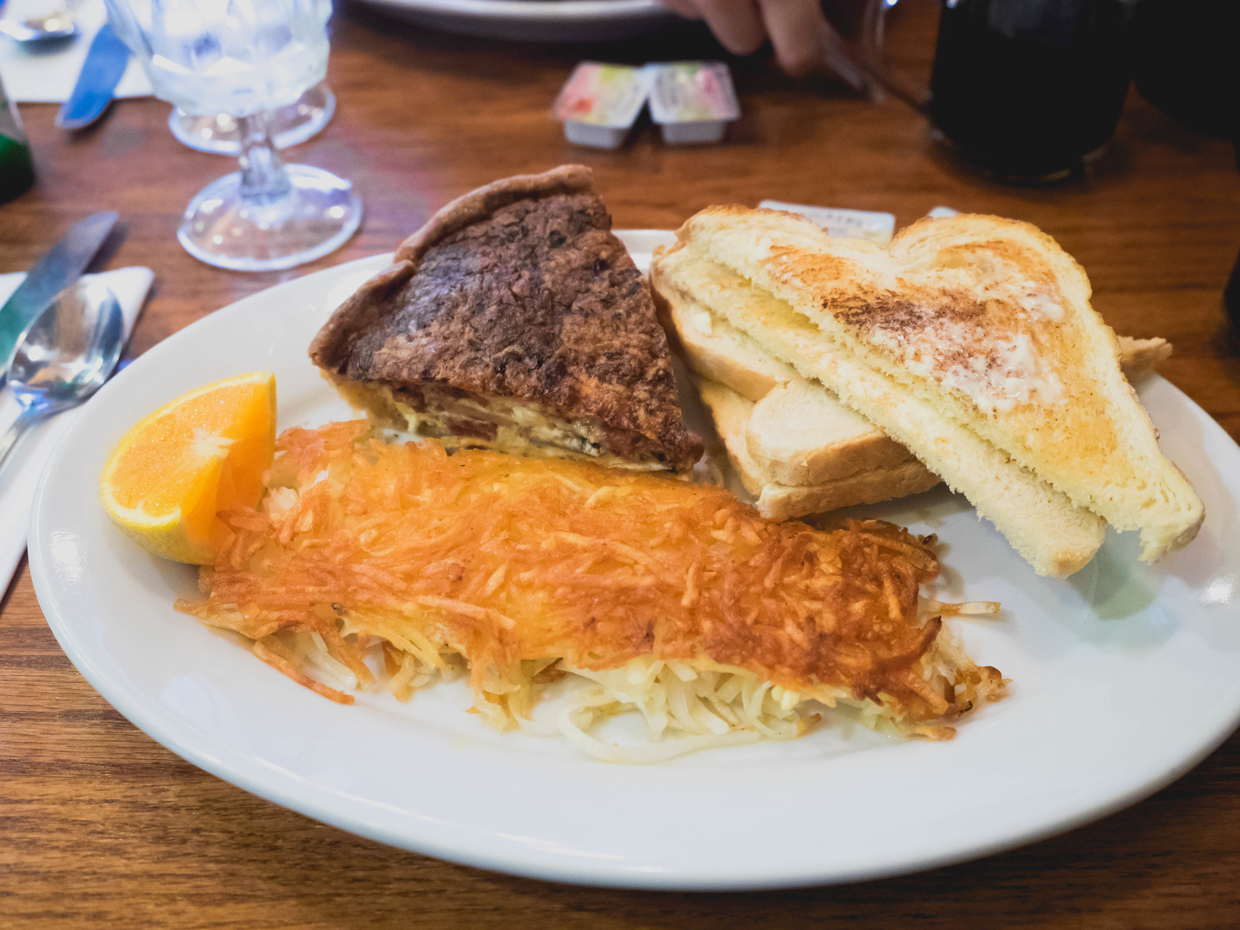 quiche  with hash browns and toast.