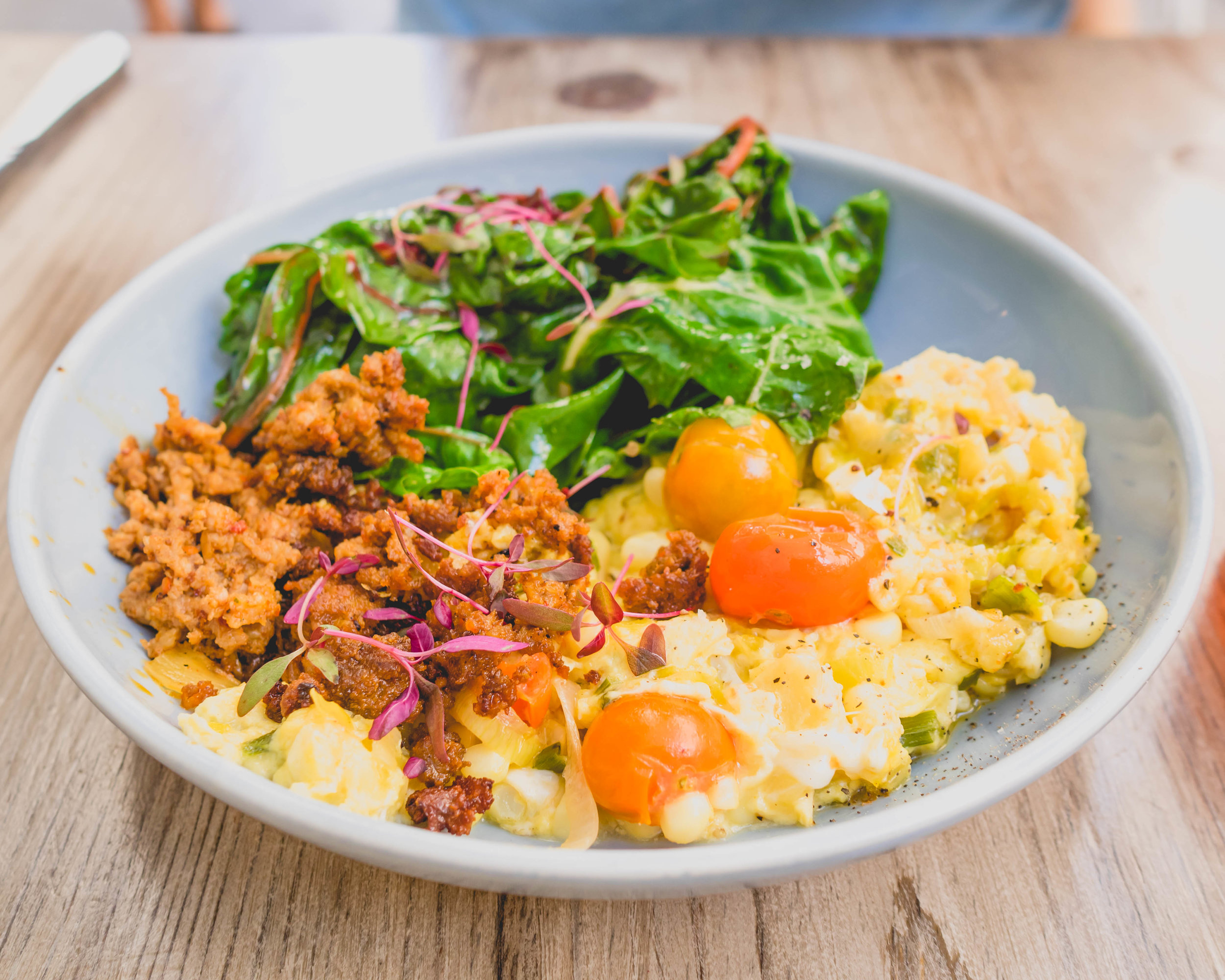 summer scramble : soft-scrambled farm eggs, house made chorizo, corn summer squash, tomatoes & basil with sauteed green on the side.