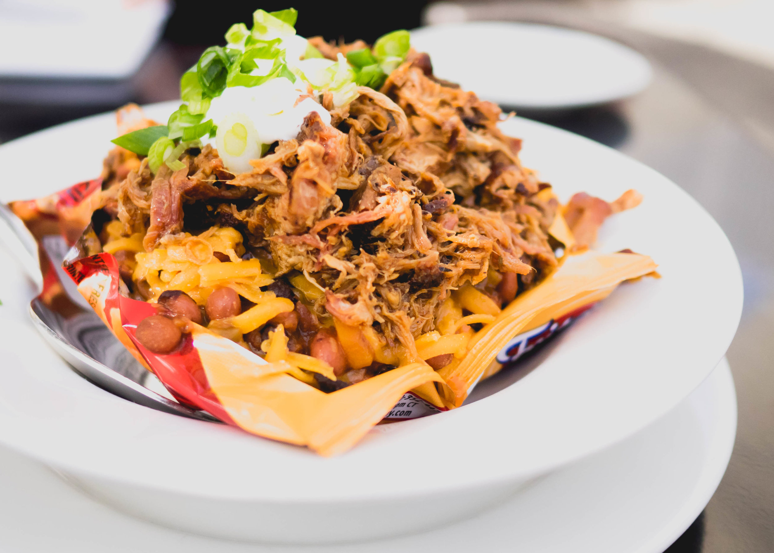 frito pie : bag of fritos topped with chili, triple chop of BBQ meats, cheddar cheese, sour cream, green onions